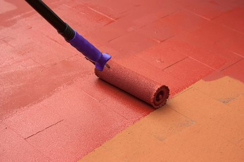 Contract painter painting a floor on color red